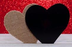 Deux coeurs différents avec un fond brillant rouge Photo libre de droits