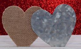 Deux coeurs différents avec un fond rouge brillant Image libre de droits
