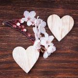 Deux coeurs en bois avec des fleurs de fleurs de cerisier de ressort Photo libre de droits