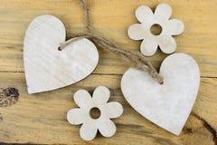 Deux coeurs en bois avec sur du vieux bois se tenant avec la corde Photos stock