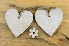 Deux coeurs en bois avec sur du vieux bois se tenant avec la corde Image stock