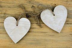 Deux coeurs en bois avec sur du vieux bois se tenant avec la corde Images stock
