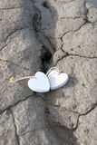 Deux coeurs en bois d'amour sur la banque de sable Photographie stock libre de droits
