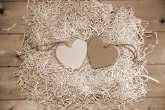 Deux coeurs en bois de sépia dans le nid Photographie stock