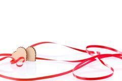Deux coeurs Deux coeurs en bois et ruban rouge de fête sur un fond blanc, jour du ` s de Valentine Fond de célébration Photos stock