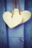 Deux coeurs en bois s'arrêtant sur le fond bleu images libres de droits