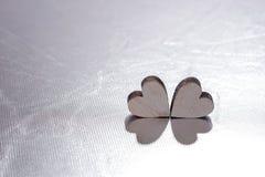 Deux coeurs en bois sur le fond argenté, concept pour l'amour Photographie stock libre de droits