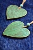 Deux coeurs en bois sur le fond bleu de denim Photographie stock libre de droits