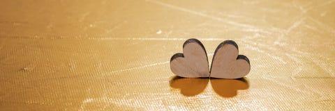 Deux coeurs en bois sur le fond d'or, concept pour l'amour Image libre de droits