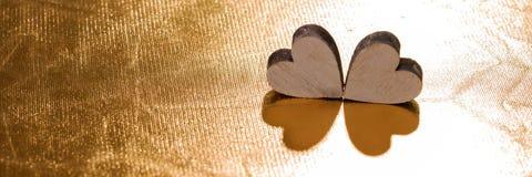 Deux coeurs en bois sur le fond d'or, concept pour l'amour Photographie stock libre de droits