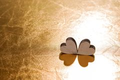 Deux coeurs en bois sur le fond d'or, concept pour l'amour Photos stock