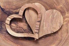 Deux coeurs en bois sur un conseil en bois olive Image stock