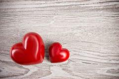 Deux coeurs en pierre rouges sur le fond neutre, l'espace des textes Photos stock
