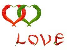 Deux coeurs et amours de mot composés de poivrons de piment rouges et verts Photo stock