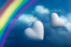 Deux coeurs et arcs-en-ciel contre un ciel bleu Images stock