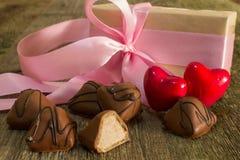 Deux coeurs et bonbons au chocolat rouges avec un cadeau Photo stock