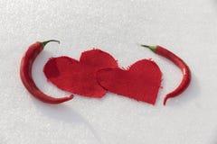 Deux coeurs et deux poivrons de piment dans la neige Photos libres de droits