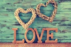 Deux coeurs et lettres en bois formant le mot aiment Photographie stock libre de droits