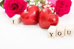 Deux coeurs et roses rouges, et cubes en bois avec des mots I et vous, sur le fond blanc Photo libre de droits