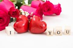 Deux coeurs et roses rouges, et cubes en bois avec des mots I et vous, sur le fond blanc Images stock