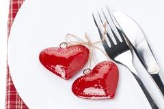 Deux coeurs, fourchettes et couteaux rouges d'un plat blanc, foyer sélectif Photographie stock libre de droits