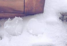 Deux coeurs glacials sur la neige près de la fenêtre, composition en jour du ` s de valentine Images stock