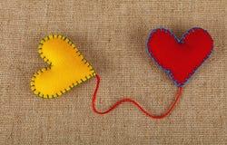 Deux coeurs, jaunes et rouges de métier de feutre sur la toile Photographie stock libre de droits