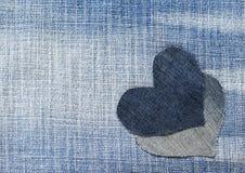 Deux coeurs ont coupé du denim bleu à un arrière-plan élégant Photo libre de droits
