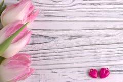 Deux coeurs pourpres avec les tulipes roses sur le blanc ont peint le fond en bois blanc rustique Jour de Valentine Photos libres de droits