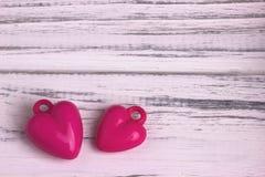 Deux coeurs pourpres sur le gris ont peint le fond en bois blanc rustique Jour de Valentine Image stock