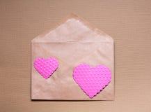 Deux coeurs roses sur le papier de métier enveloppent Photos libres de droits