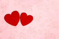 Deux coeurs rouges à l'arrière-plan floral rose de modèle photos libres de droits