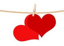 Deux coeurs rouges accrochent sur la pince à linge d'isolement sur le blanc Images stock