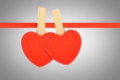 Deux coeurs rouges au ruban au-dessus du bruit de gamme de gris Images stock