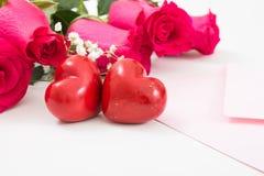 Deux coeurs rouges avec l'enveloppe rose et les roses rouges Image libre de droits