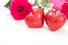 Deux coeurs rouges avec le bouquet des roses rouges, sur le blanc Photo stock