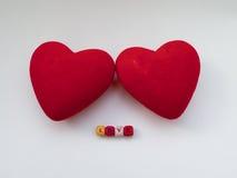 Deux coeurs rouges avec le mot AIMENT des lettres colorées Image stock