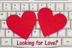 Deux coeurs rouges avec le texte recherchant l'amour sur un clavier photos libres de droits