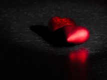 Deux coeurs rouges décoratifs sur la lumière foncée noire et sur la table en bois, concept de Saint Valentin Photographie stock