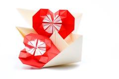 Deux coeurs rouges d'origami dans un bateau jaune de papier sur un fond blanc Photos stock
