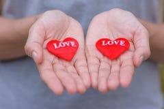 Deux coeurs rouges dans des mains Photographie stock libre de droits