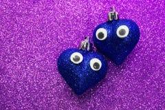 Deux coeurs rouges dans l'amour avec des yeux dans le d'or lumineux de fond Photos stock