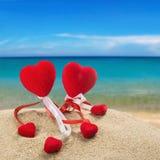 Deux coeurs rouges dans le sable sur le fond d'océan Photographie stock libre de droits