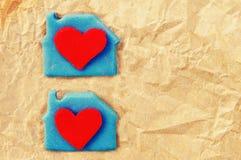 Deux coeurs rouges dans une loge sur le papier jaune chiffonné Carte de fête romantique Photo libre de droits