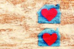 Deux coeurs rouges dans une loge sur le papier jaune chiffonné Carte de fête romantique Images stock