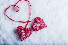 Deux coeurs rouges de beau vintage attachés ainsi qu'un ruban sur un fond blanc de neige Amour et concept de jour de valentines d Photos libres de droits