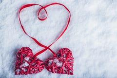 Deux coeurs rouges de beau vintage attachés ainsi qu'un ruban sur un fond blanc de neige Amour et concept de jour de valentines d Photos stock