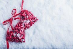 Deux coeurs rouges de beau vintage attachés ainsi qu'un ruban sur un fond blanc de neige Amour et concept de jour de valentines d Image stock