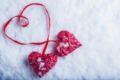 Deux coeurs rouges de beau vintage attachés ainsi qu'un ruban sur un fond blanc de neige Amour et concept de jour de valentines d Images libres de droits