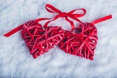 Deux coeurs rouges de beau vintage attachés ainsi qu'un ruban sur un fond blanc de neige Amour et concept de jour de valentines d Images stock